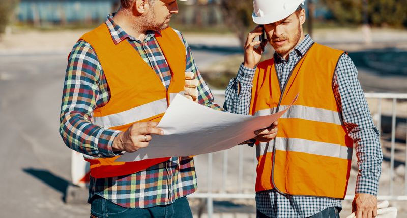 two paving construction workers talking about project plans
